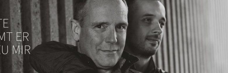 """Motiv 5 zeigt zwei junge Männer, der eine hälte den anderen von hinten im Arm, beide lächeln. Dazu der Gedanke: """"Heute kommt er mit zu mir"""""""