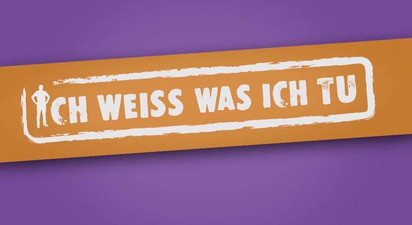 """Auf einem gelben Banner vor violettem Hintergrund befindet sich ein weißer Stempel mit der Aufschrift """"ICH WEISS WAS ICH TU"""". Das erste """"I"""" hat eine menschliche Gestalt."""