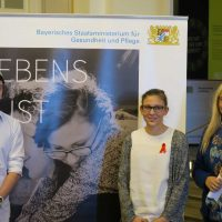Melanie Huml mit zwei Protagonisten des Fotowettbewerb vor dem Motiv 9