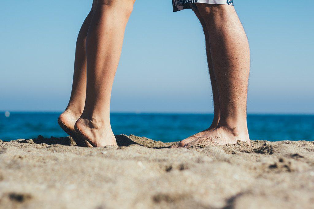 zwei Füsse im Sand, am Strand, das Meer im Hintergrund - vermutlich ein Pärchen das sich küsst, aber es sind nur die Beine zu sehen...