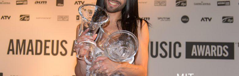 Conchita Wurst mit SiegerPokal des Amadaeus Music Awards vor einer Fotowand der Preisverleihung