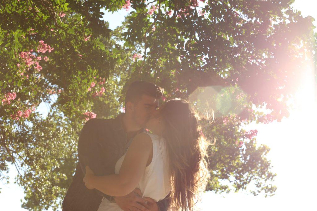 Küssendes Paar unter blühendem Baum im Sonnenlicht