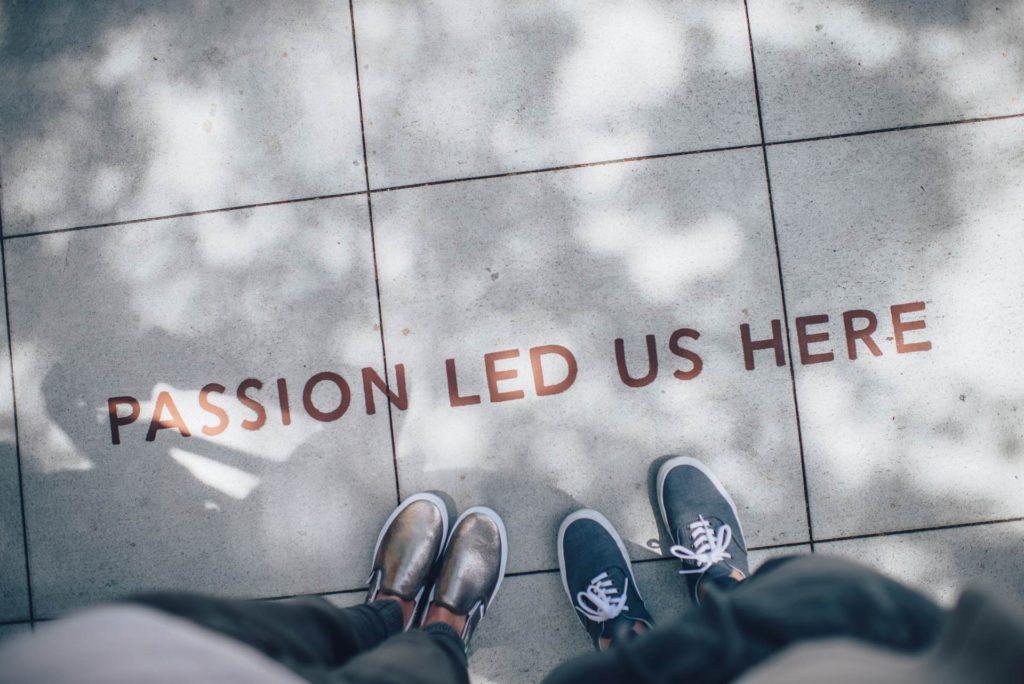 Zwei Leute stehen vor dem Schriftzug PASSION LED US HERE, der auf den Boden geschrieben steht.
